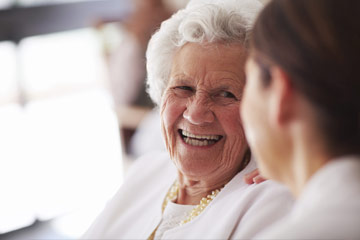 Senior woman smiling at caregiver