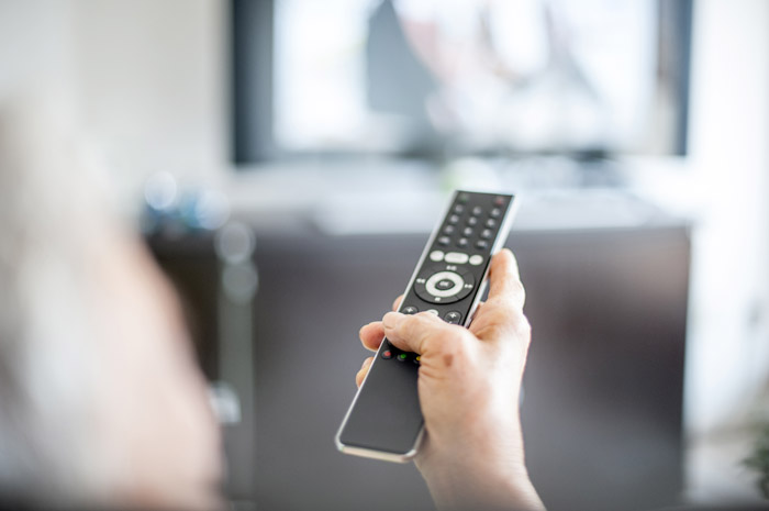 A person pointing a TV remote at the TV